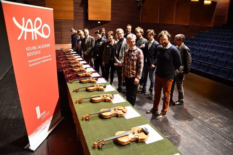 Professor*innen der hmt Rostock, Geigenbauer und Studierende vor der großen Auswahl an exzellenten Geigen und Bratschen. Foto: Angelika Thönes